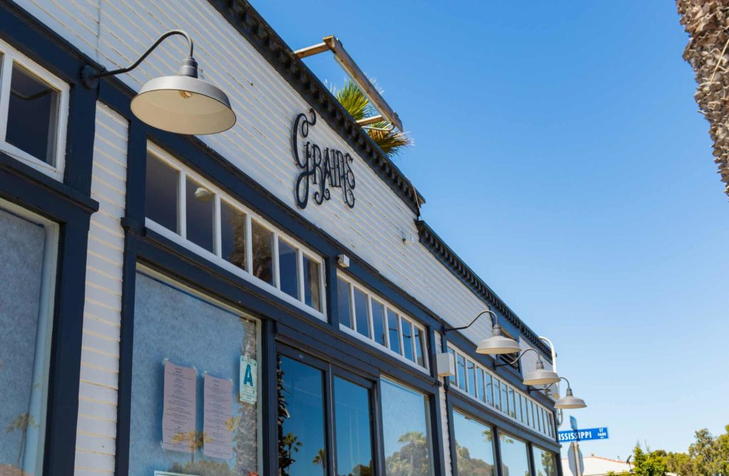 The front of Grains vegan restaurant in University Heights. It is a white restaurant with black trim and a Grains logo in the center.