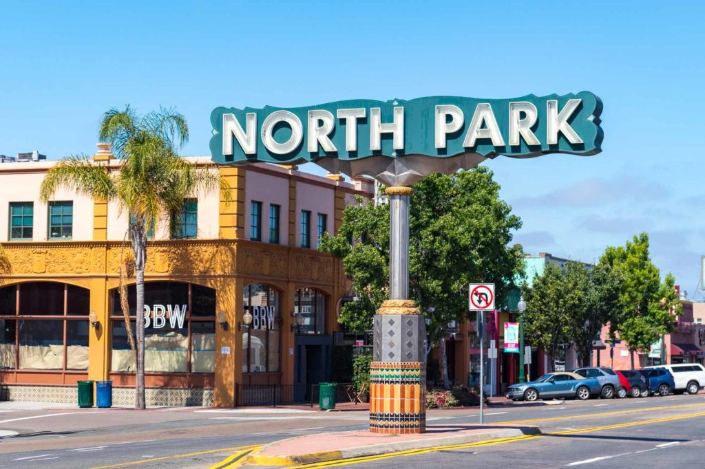 The blue North Park Sign standing in the middle of University Avenue