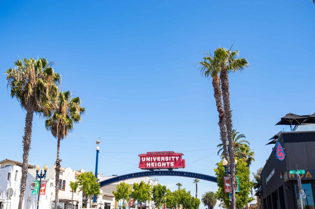 University Heights sign with red trolley and blue arch above Park BLVD.