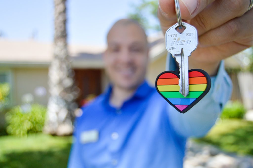 An close up photo of a colorful heart keychain and a set of keys being held by a real estate agent in the background who is out of focus, and a ranch style home with palm trees in the front yard